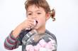 Little girl eating marshmallow
