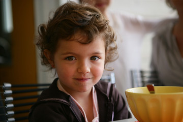 Little girl sat at the breakfast table