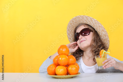 Little girl with freshly squeezed orange juice