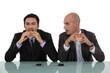 Businessmen eating burgers