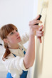 Woman carefully painting wall with roller