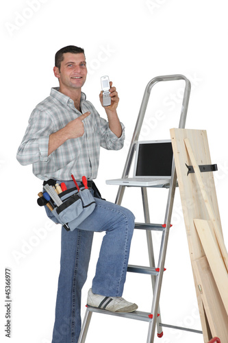 Carpenter posing by step-ladder