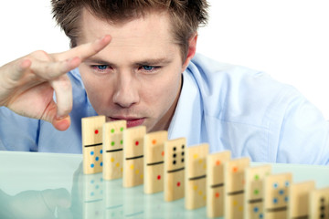 Businessman flicking dominoes