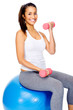 Gym woman on ball with dumbbells