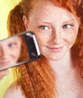 Freckled girl is taking a self portrait with a mobile phone