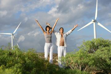 Man and woman stretching near wind turbines
