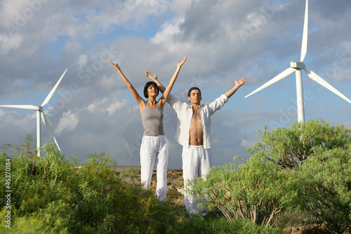 Man and woman stretching near wind turbines