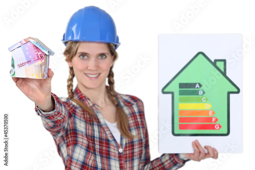 Tradeswoman holding an energy efficiency rating sign