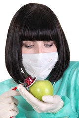 nurse examining an apple with a stethoscope