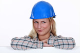 happy-looking blonde craftswoman with arms resting on board