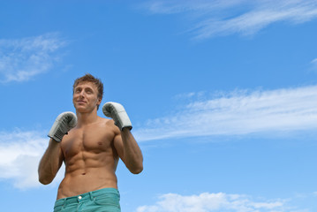 Young guy in boxing gloves training outdoors