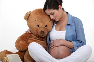 Pregnant woman sat with large teddy bear