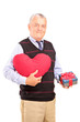 A mature gentleman holding a red heart shaped object and gift
