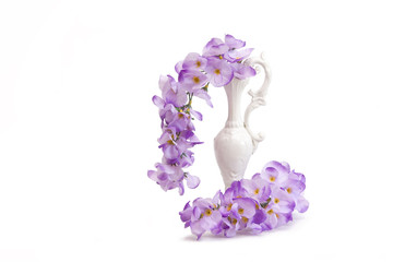 Artificial wisteria flowers in white ornament pitcher