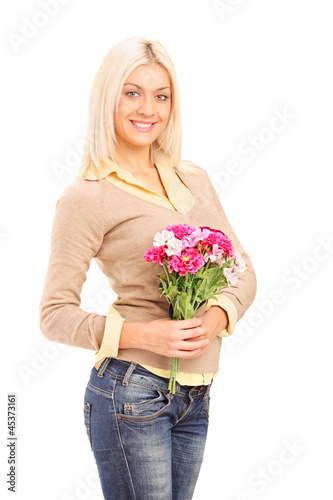 A smiling blond woman holding a bunch of flowers