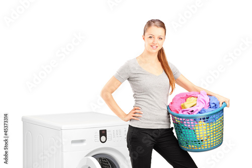 Smiling woman with laundry basket posing next to a washing machi