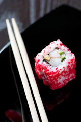 Vertical shot of a sushi roll and chopsticks, close-up
