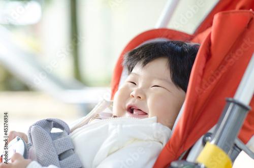 ベビーカーで笑っている赤ちゃん