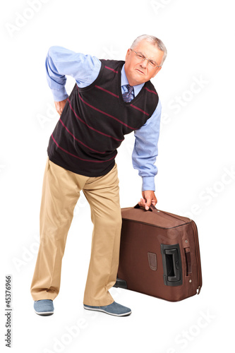 Senior man lifting his luggage and suffering from a back pain