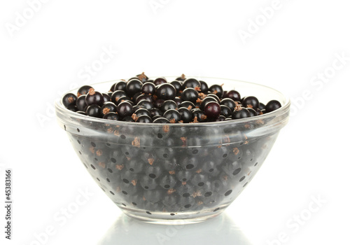 Fresh black currant in transparent bowl isolated on white