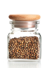 Jar of coriander seeds isolated on white