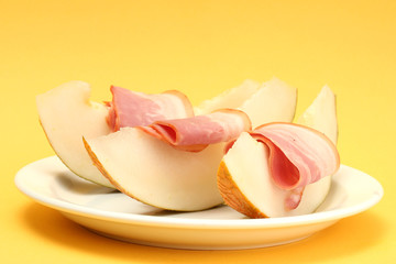 parma ham and melon, on yellow background