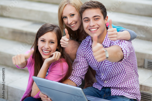 Friends with laptop showing thumbs up