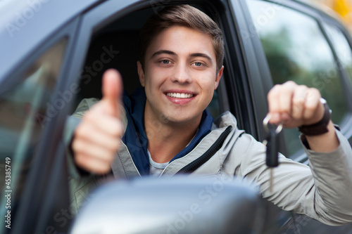Young man sitting in car holding car keys