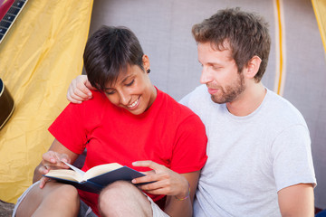 Young Couple Camping and Reading a Book
