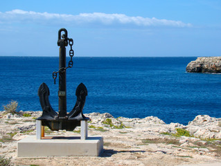 A big black anchor located on the coast