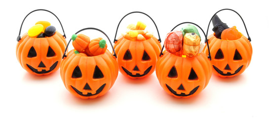 Five jack-o-lantern candy holders filled with a variety of candy