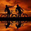 two cyclists silhouette in sunset