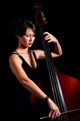 Woman play classic contrabass using bow