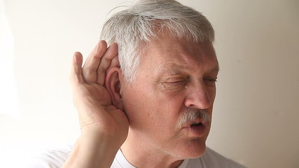 older man strains to hear what someone is saying