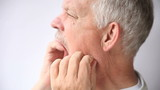 older man experiencing pain either in his teeth or jaw joint