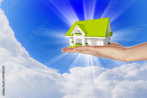 the house in hands on blue sky
