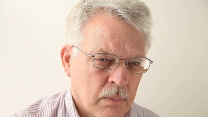 senior man with glasses experiencing fatigue and blurry vision