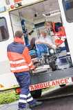 Paramedics putting patient in ambulance car aid