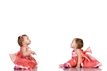 Identical twin baby girls looking  at something in birthday