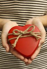 Red heart in girl hands