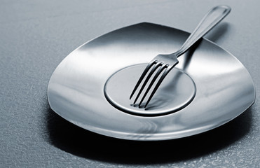 Empty steel plate with fork on the table