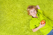 Child lying on green carpet, holding apple