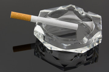 A cigarette in an ashtray against a dark background.