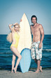 Couple at the beach with surfboard.