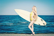 Beautiful young surf girl portrait at the beach with a surfboard