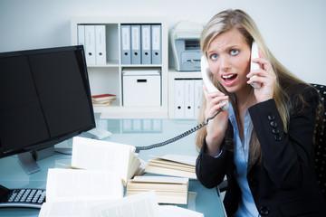 gestresste geschäftsfrau auf zwei leitungen