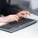 frau tippt auf einer tastatur