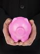 mans hand holding a pink piggy bank