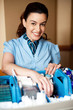 Cheerful executive standing behind the housekeeping cart