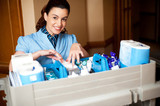 Working staff arranging toiletries in a wheel cart poster